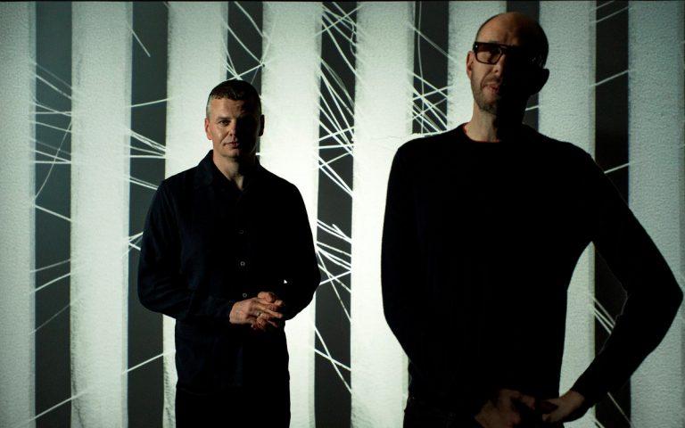 zwei Männer vor gestreiftem Hintergrund