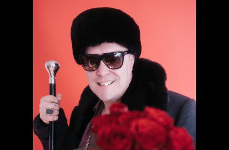 Der Rapper Morlockk Dilemma mit Sonnenbrille, einen Strauß Rosen, edlen Gehstock und in schwarzer Mütze, Mantel und Sonnenbrille.
