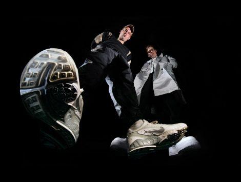Froschperspektive von Grim104 und Testo vor schwarzem Hintergrund (Hip Hop Duo Zugezogen Maskulin)