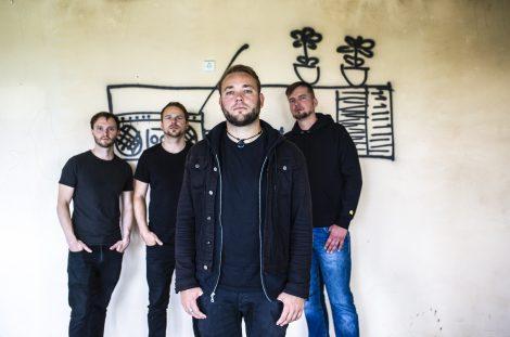 Vier Mitglieder der Band Larrikins vor heller Wand mit schwarzer Graffiti-Zeichnung