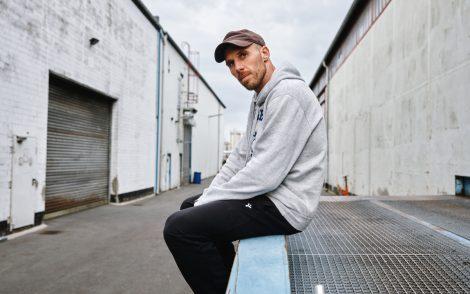 Musiker Mal Élevé ist auf Lüftungschacht zwischen Häusern in einem Industriegebiet