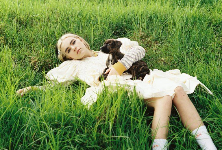 Musikerin BENEE liegt auf grüner Wiese mit Hundewelpen im Schoß