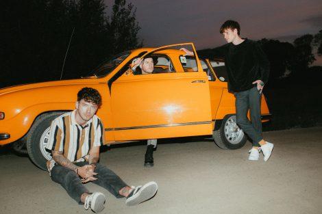 Mitglieder der Band Normandie sitzen/stehen um/in orangefarbenen Auto mit geöffneter Fahrertür
