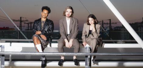 Mile, Marco Kleebauer und Katrin Paucz von der Band Sharktank sitzen von links nach rechts auf einer Brücke