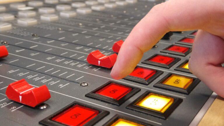 Zeigefinger über On-Taste auf Audio-Mischpult im LOHRO-Sendestudio