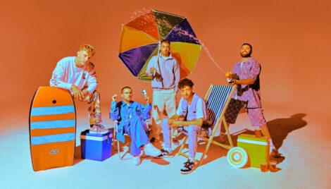 Mitglieder der Band easy life posieren mit Strandutensilien in Studiokulisse