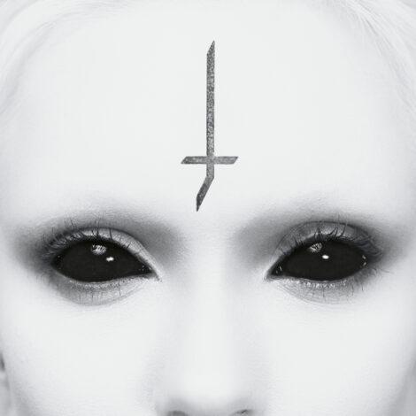 Ein weißes Gesicht mit schwarzen Augen, auf der Stirn das J-Kreuz nach unten