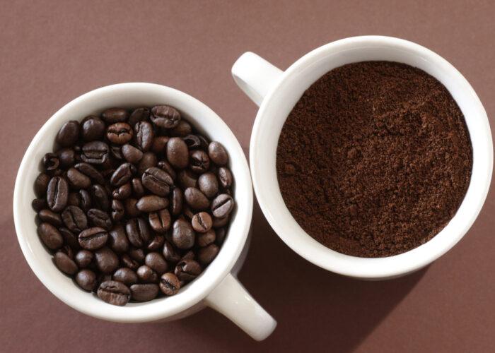 Draufsicht zwei weiße Kaffetassen mit Kaffeebohnen bzw- Kaffeepulver gefüllt
