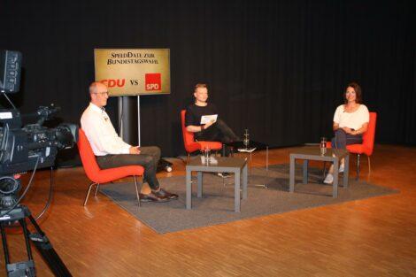 """Peter Stein, Moderator Alex und Katrin Zschau sitzen im Halbkreis Richtung Kameras. Im Hintergrund steht ein Monitor mit der Aufschrift """"SpeedDate zur Wahl: CDU vs SPD"""""""