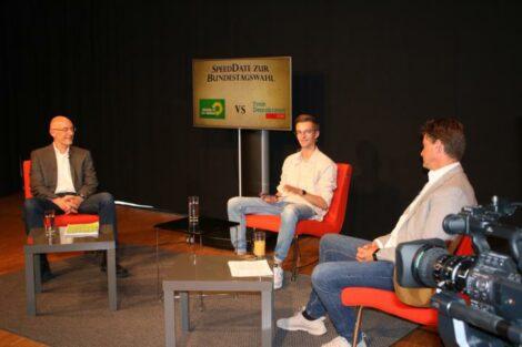 """Andreas Tesche, Moderator Konrad und Hagen Reinhold sitzen im Halbkreis Richtung Kameras. Im Hintergrund steht ein Monitor mit der Aufschrift """"SpeedDate zur Wahl: GRÜNE vs FDP"""""""