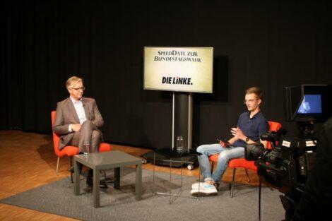"""Dietmar Bartsch und Konrad sitzen sich schräg gegenüber. Hinter ihnen ein Monitor mit der Aufschrift """"SpeedDate zur Wahl: Die Linke""""."""